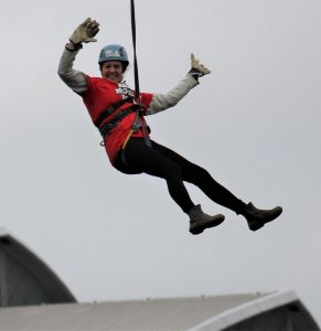 Lady on zip slide waving with both hands.